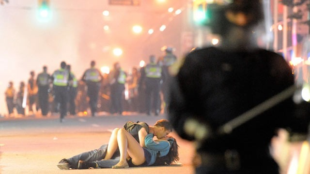 Two people lie in the middle of the road kissing. Riot police are in the foregroud and background.