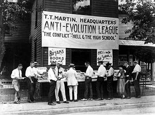 "A large sign hangs reading, ""Anti-Evolution League, The Conflict - Hell and the High School"""