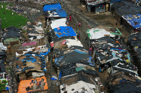 Dilapidated slum dwellings with tarps weighed down with tires used as roofs.