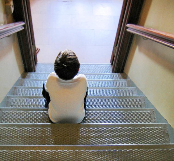 A child is shown from behind sitting on stairs looking into a room.