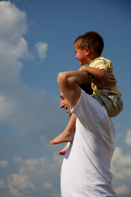 A young boy sits on the shoulders of a man who holds him in place.
