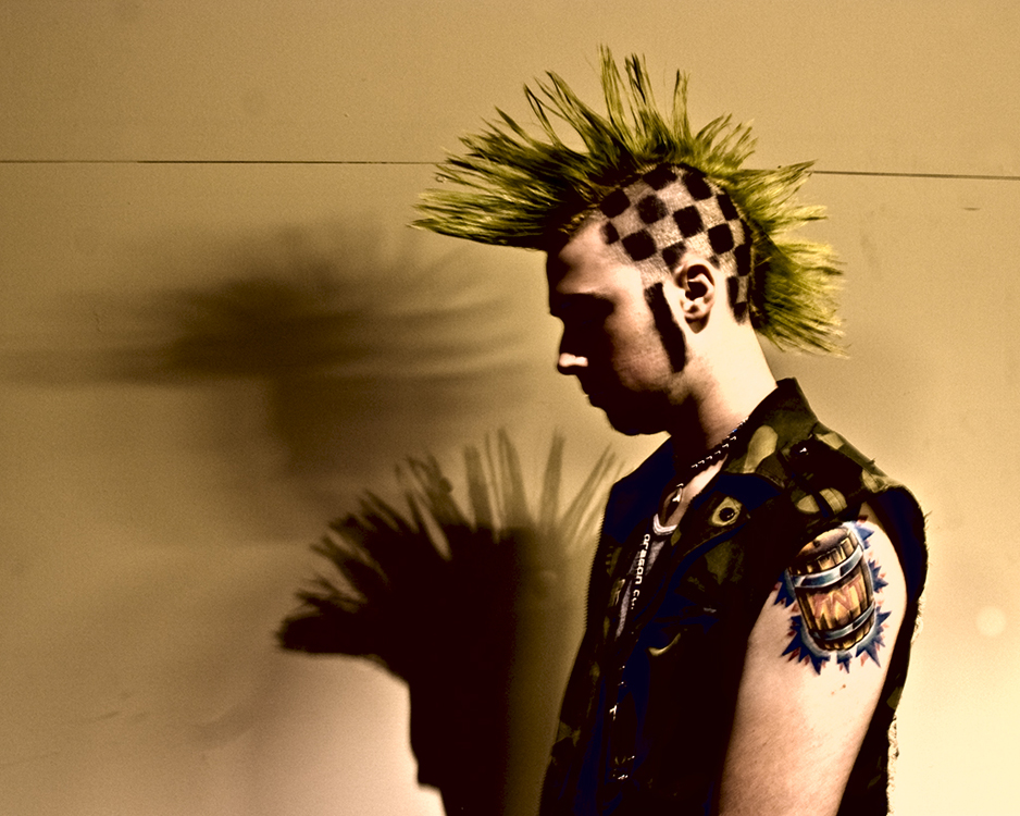 A young man with tattoos, a leather vest, and a spiky Mohawk haircut.