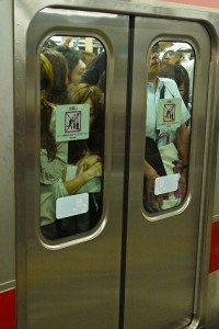A train so full that people are pressed up against the doors.