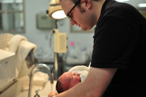 A man washing a baby's hair under the tap.