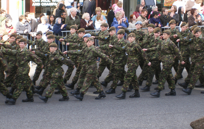 A group of young cadets in a parade wearing the same uniforms march in sync.