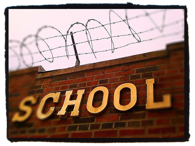 A school wall topped with barbed wire fence.