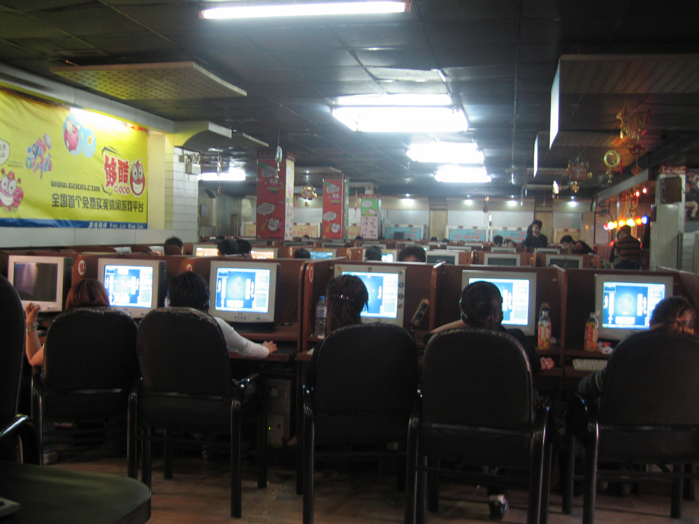 Rows of people at computers in a café
