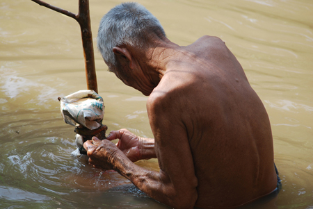 An old man standing in a lake or river. He appears to be fixing something.