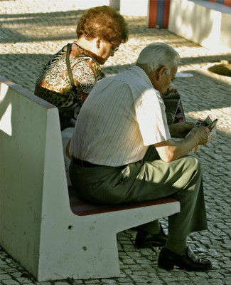 An older man and older woman sit side by side on a street bench reading.