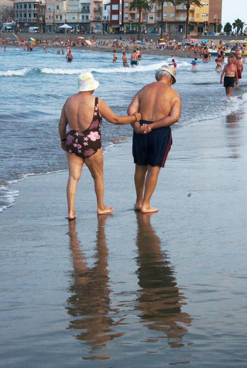 An older couple in bathing suits walk arm in arm along a beach.