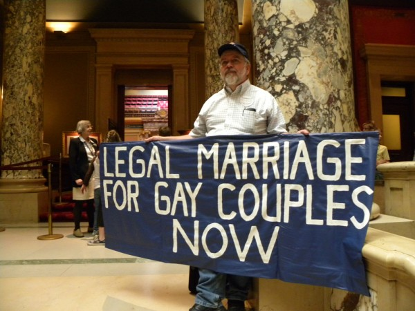 "A man holding a sign that says, ""Legal marriage for gay couples now."""