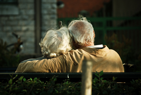 An old couple sitting on a park bench leaning into each other.