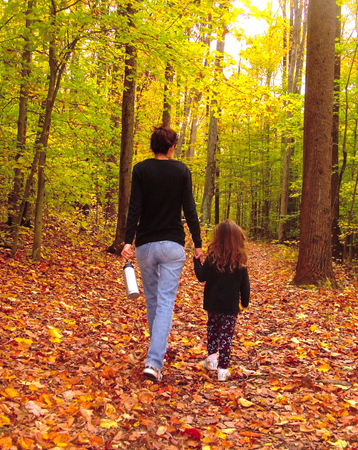A woman walks through a forest holding the hand of a young girl.