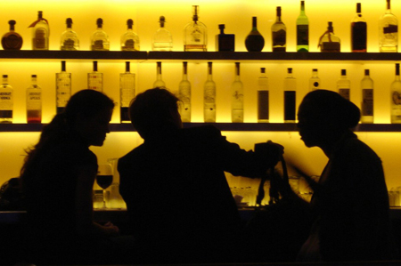 Three people sitting at a bar.