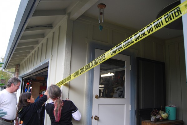 People putting up crime scene tape around a house.