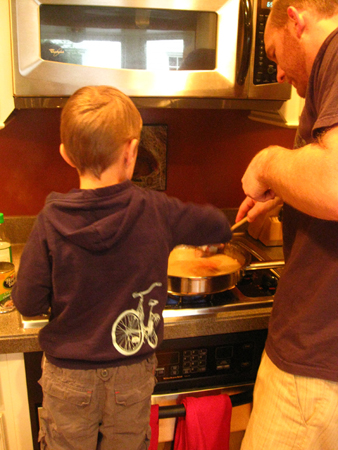 A young boy stands at a stove beside a man helping stir a pot.