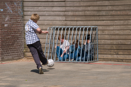 Young kids hide behind a hockey net while another boy kicks a ball at them.