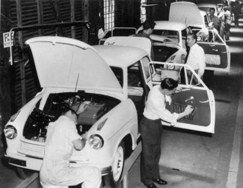 A black and white photo of people working on a car assembly-line.