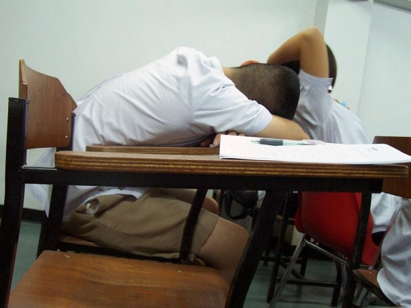 A boy with his head down sleeping on his school desk.