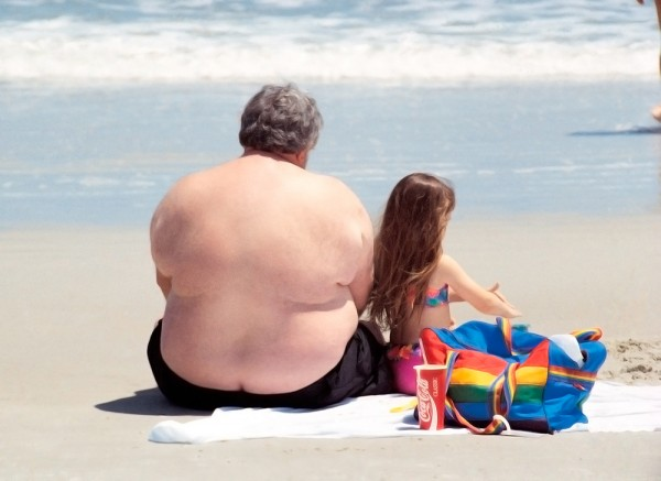 An overweight older man sits on a beach in his swimsuit beside a young girl playing in the sand.