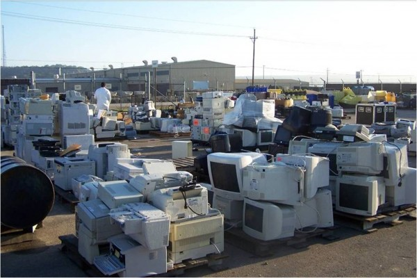 Piles of computer monitors, printers, microwaves, and hard drives.