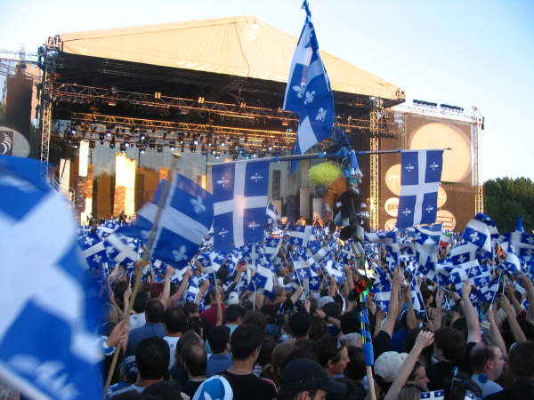 A crowd of people stand in front of a stage. Many hold Quebec flags in the air.