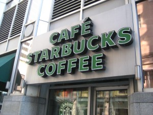 "A Starbucks store front with ""coffee"" spelt in english and french."