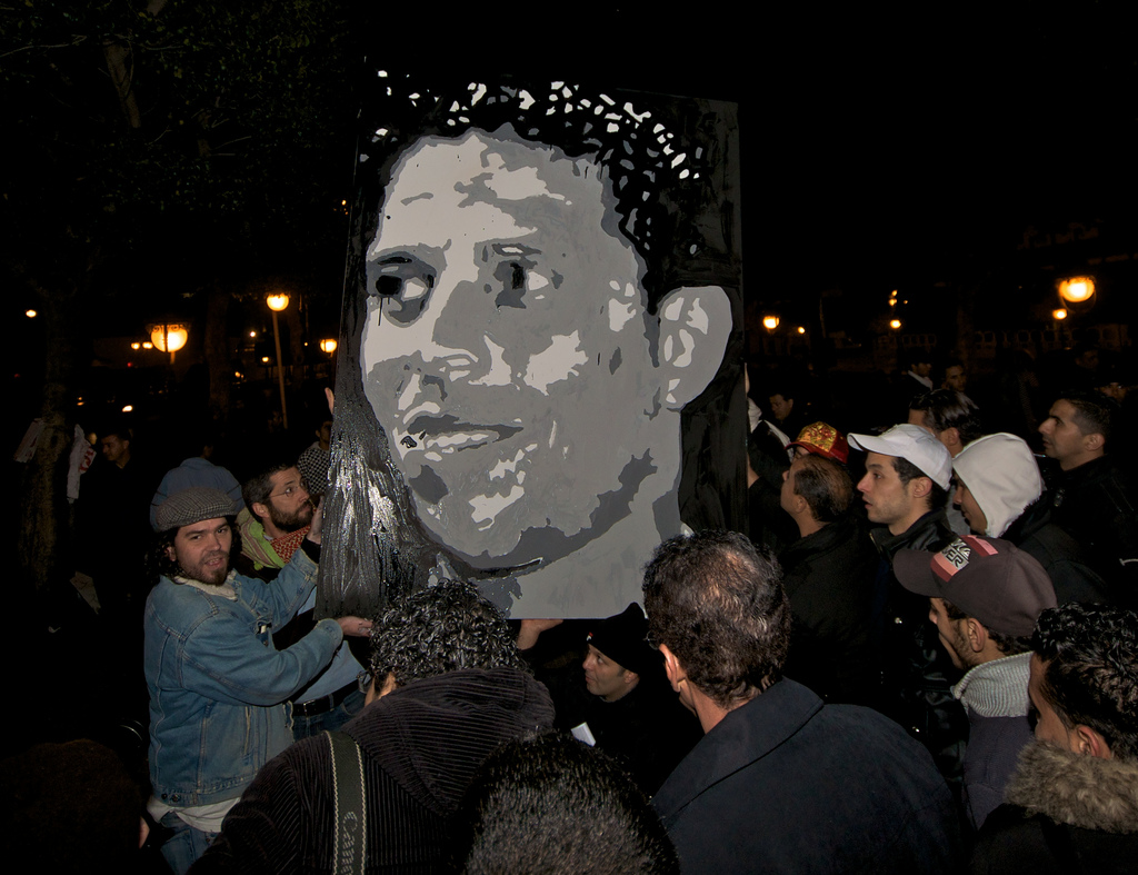 A group of people holding up an image of Mohamed Bouazizi.