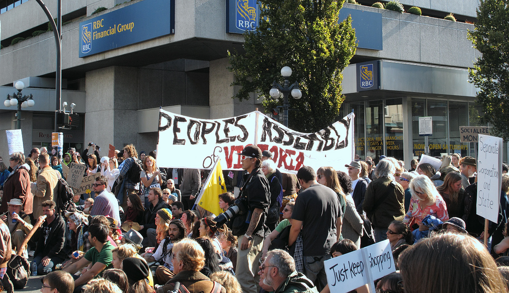 "A large crowd of people gathered on the street. One sign says, ""Peoples Assembly of Victoria."""