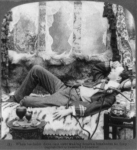 A man laying on a couch of furs beside an opium pipe.