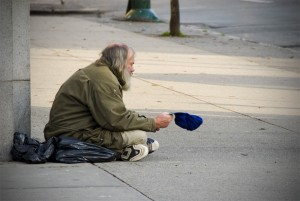 An old man in ratty clothes sits on the corner of the street holding out a hat for money.