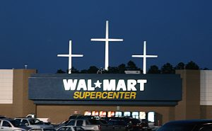 The storefront of a Walmart supercenter with three large crosses behind it.