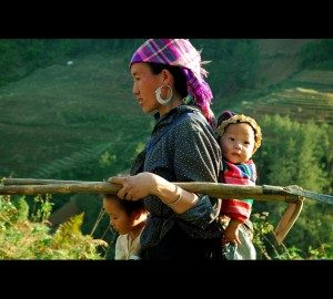 A woman carries tools in one arm with a baby on her back and a young girl by her side.