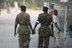 Two men in army uniforms walk down the street holding hands