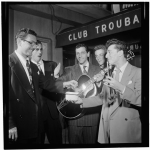 Black and white photo of young men in suits. Two of the men hold musical instruments.