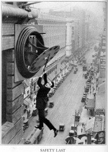 Harold Lloyd hangs from a broken clock above a New York City street in the film, Safety Last.