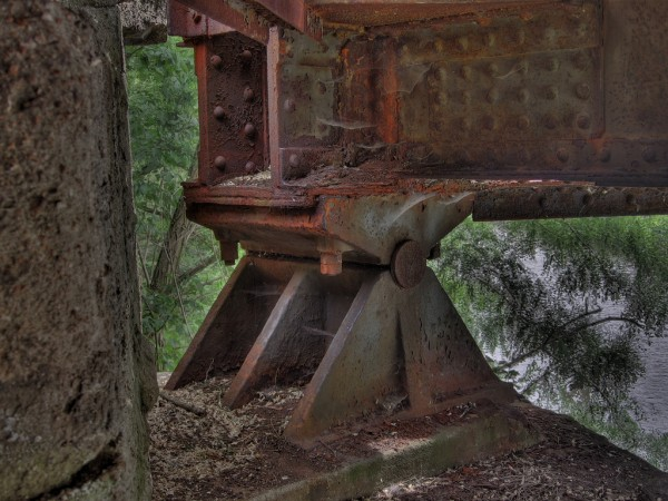 "These support beams on a bridge are obviously rusted. If the rusting becomes too bad, it will compromise the integrity of the bridge, requiring replace- ment. Source: ""rusty bridge bearing"" by Fabian is licensed under the Creative Commons Attribution-NonCommercial-ShareAlike 2.0 Generic"