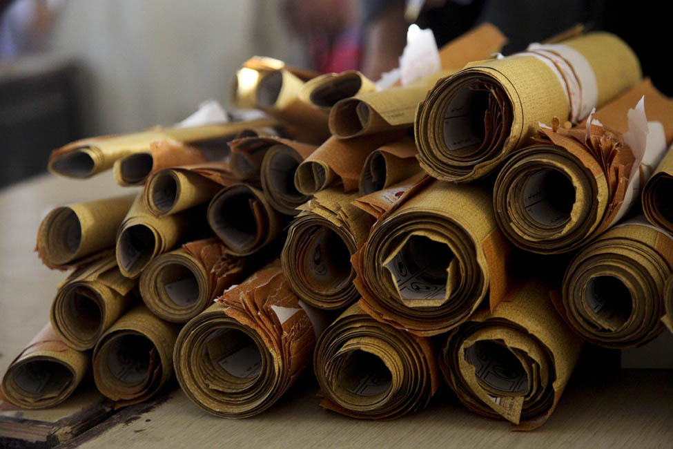 This photo shows about 26 rolls of paper piled together. The rolls are different sizes.