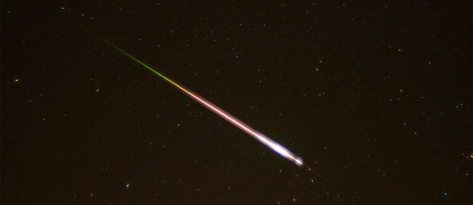 This is a photo taken of the night sky. A meteor and its tail are shown entering the earth's atmosphere.