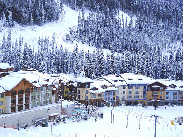 A large hotel at the bottom of a ski hill in winter.
