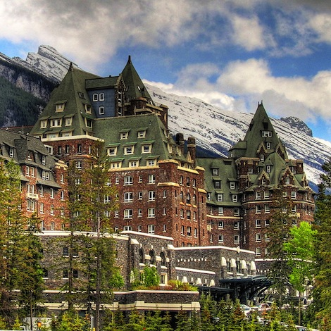 The Banff Springs Hotel is a large, castle like hotel with red walls and green, pointy roofs.