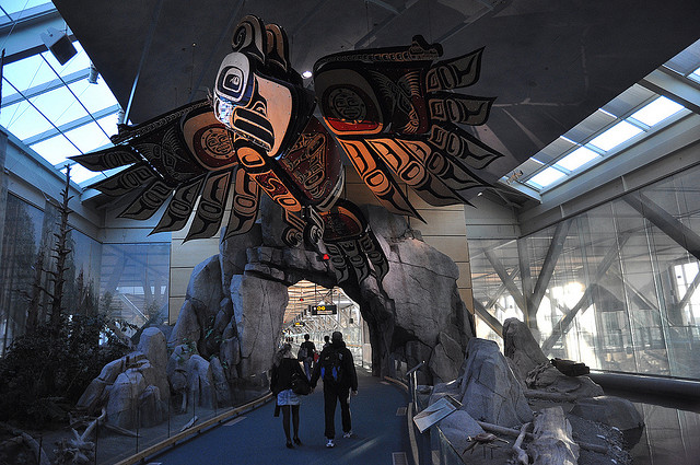 A large Haida eagle sculpture hangs from the ceiling.