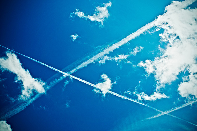 The contrail from a plane streaks across a blue sky.