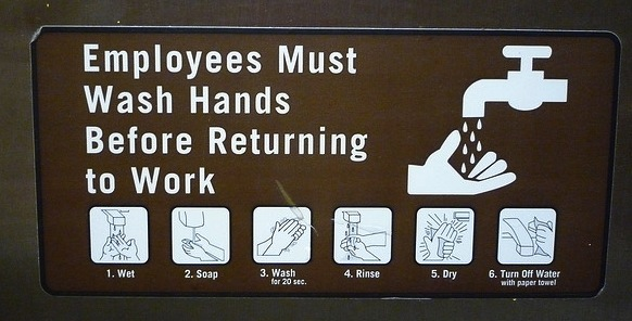 "A sign saying, ""Employees Must Wash Hands Before Returning to Work."""