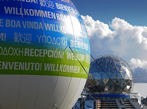 "A large sign outside of science world with ""welcome!"" in many different languages."