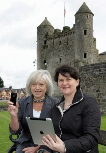 Two woman in front of an old castle. The woman on a right holds an ipad.