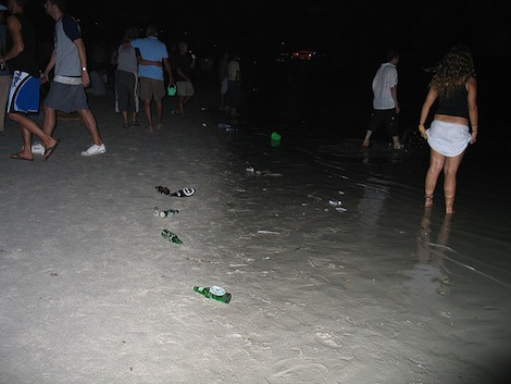 Young people on a beach at night drinking with beer bottles lying in the sand.
