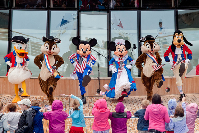 People dressed up in disney costumes perform for a crowd of children.
