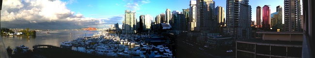 A harbour filled with boats in front of Vancouver's tall city buildings