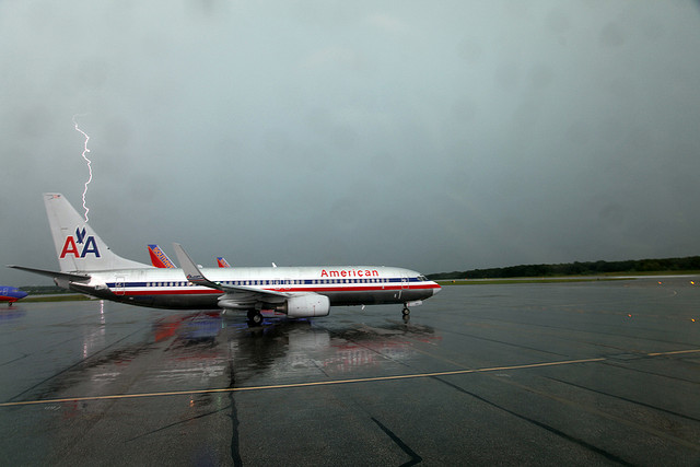 An air plane on a wet runway with lightning in the background.